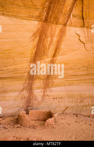 Ancient Ancestral Puebloan historic site structure with pairs of handprint pictographs on the back mineral stained sandstone wall in southeastern Utah - Stock Photo