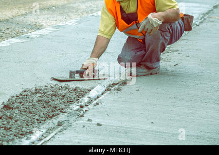 Mason leveling concrete with trowel, hands spreading poured concrete. Vintage style. - Stock Photo
