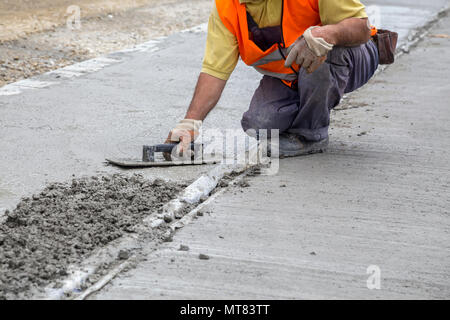 Mason leveling concrete with trowel, hands spreading poured concrete. - Stock Photo
