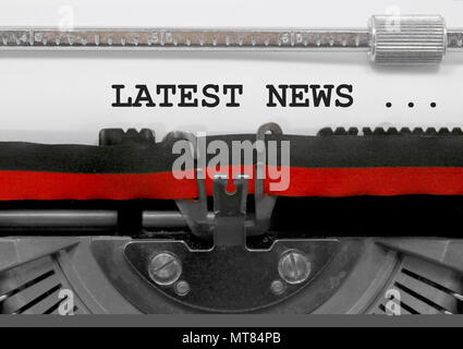 Latest news phrase text written by an old typewriter on white sheet - Stock Photo
