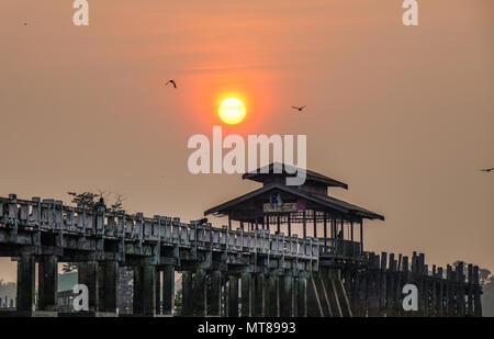Mandalay, Myanmar - Feb 22, 2016. View of U Bein Bridge at sunrise in Mandalay, Myanmar. - Stock Photo