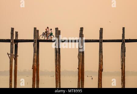 Mandalay, Myanmar - Feb 22, 2016. People on U Bein Bridge at sunrise in Mandalay, Myanmar. - Stock Photo