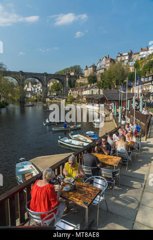 Blue sky & people eating at riverside cafe & boating in rowing boats on River Nidd by bridge - scenic sunny summer day, Knaresborough, England, UK. - Stock Photo
