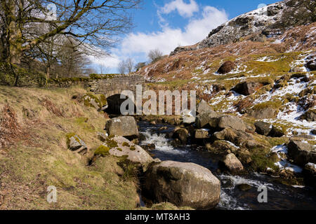 Scenic rural view of blue sky, winter snow & small, rustic, stone, footbridge over stream -  Hebden Beck, Hole Bottom, Yorkshire Dales, England, UK. - Stock Photo