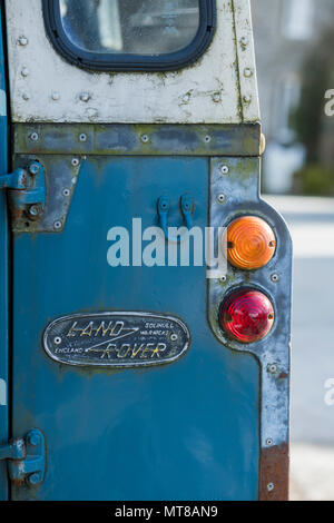 Close-up detail of blue & white classic vintage 4wd Land Rover with badge on the back & two rear lights (red & orange) - Yokshire, England, UK. - Stock Photo