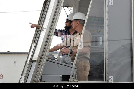Mike McLachlan, Underway Replenishment mechanical engineer, guides Moore during a hands-on demonstration of the Heavy Electric Standard Tensioned Replenishment Alongside Method, March 10. - Stock Photo