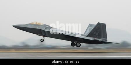 A F-22 Raptor from Joint Base Elmendorf-Richardson, Alaska, takes off from Gwangju Air Base, Republic of Korea, Dec. 04, 2017. The fighter aircraft is participating in the pinensula-wide routine exercise, Vigilant Ace-18 -- an exercise focused on interoperability. (U.S Air Force photo by Senior Airmnan Jessica H. Smith) - Stock Photo
