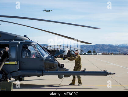 An Airman with the 943rd Rescue Group performs a pre-flight inspection on an HH-60G Pave Hawk helicopter as HC-130J Combat King II flies over head, March 3, 2017, at Gowen Field, Idaho, during pre-deployment training for the 305th Rescue Squadron. The 305th RQS, located at Davis-Monthan Air Force Base, Ariz., is conducting training at the Idaho Air National Guard's Orchard Combat Training Center, a 143,000-acre live-fire range located south of Boise, Idaho, to hone all of their search and rescue procedures before heading to Southwest Asia. (U.S. Air Force photo/Staff Sgt. Jared Trimarchi) - Stock Photo
