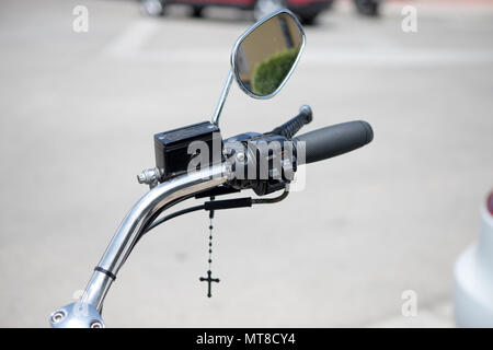 Handlebar Harley Davidson detail with hanging cross - Stock Photo