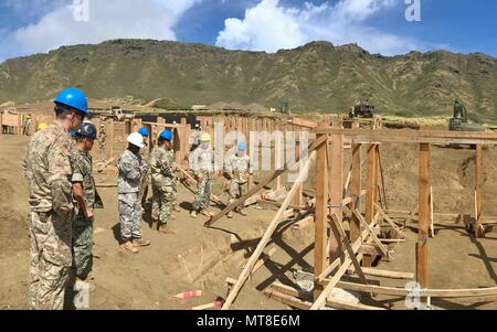 Service members with the 8th Theater Sustainment Command observe construction of trenches at the Kaneohe Bay Gun Training Facility at Marine Corps Base Hawaii June 14, 2017. The live fire range has been upgraded to create a combat training environment largely with materials procured by DLA Troop Support Pacific - Stock Photo