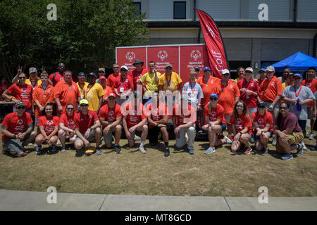 Special Olympic golf athletes and volunteers pose for a group photo at the Bay Breeze Event Center during the Special Olympics Mississippi 2018 Summer Games at Keesler Air Force Base, Mississippi, May 12, 2018. Founded in 1968, Special Olympics hosts sporting events around the world for people of all ages with special needs to include more than 700 athletes from Mississippi. (U.S. Air Force photo by Senior Airman Jenay Randolph) - Stock Photo