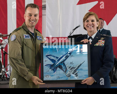 Royal Canadian Air Force Capt. Stephan Porteus presents Gen. Lori J. Robinson, commander of North American Aerospace Defense Command and U.S. Northern Command, with a lithograph at the NORAD 60th Anniversary Ceremony on Peterson Air Force Base Colorado, May 12, 2018. The ceremony and static display of various NORAD aircraft was the culmination of a three-day event, which included a media tour of Cheyenne Mountain Air Force Station, the dedication of a cairn outside the commands' headquarters building memorializing the Canadians who have passed away while serving NORAD, and a fly over in missin - Stock Photo