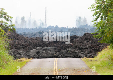 A lava roadblock covers a residential road May 12, 2018, at Leilani Estates, Pahoa, Hawaii. Members of the Hawaii Army and Air National Guard have been activated in order to assemble Task Force Hawaii, which is providing traffic assistance, presence patrols and supporting local government agencies with the volcano outbreak relief effort. (U.S. Air National Guard photo by Senior Airman John Linzmeier) - Stock Photo