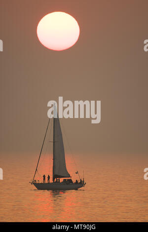 Aberystwyth Wales UK Bank Holiday Monday 28 May 2018  UK Weather: The Bank Holiday Monday comes to a close with a spectacular orange sunset over a yacht floating on the flat calm waters of Cardigan Bay, just off the beach at Aberystwyth on the west coast  of Wales   photo © Keith Morris /  Alamy Live News - Stock Photo