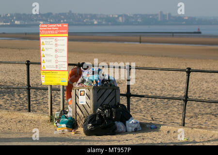 Crosby, Liverpool.  29th May, 2018. UK Weather:  Bright summer day on the north-west coast as local residents and holidaymakers take early morning exercise on the coastal path and Merseyside beach. The beach is festooned with Spring Bank Holiday litter with overflowing bins and garbage blowing in the breeze. The Sefton council containers clearly inadequate for the amount of plastic waste. Credit: MediaWorldImages/AlamyyLiveNews. - Stock Photo