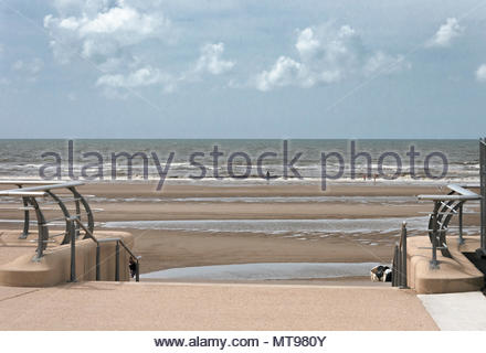 2008, An adult and a couple of children in the distance playing on an almost deserted sea front in Blackpool England, while restoration work was ongoi - Stock Photo
