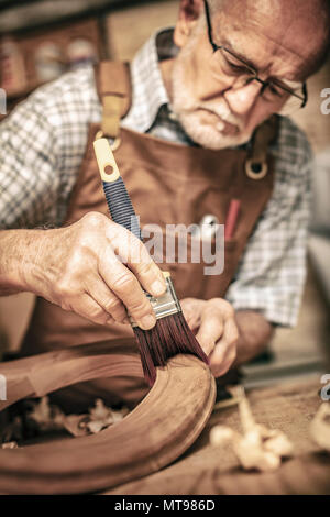 elderly carpenter uses a brush on an unfinished chair - Stock Photo