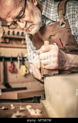 old carpenter uses a planer - Stock Photo