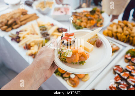 Man helping himself on Buffet of party outdoors taking food  - Stock Photo