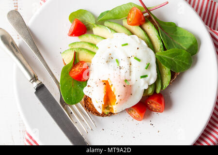 Healthy whole grain bread toast with avocado, poached egg, cherry tomato and baby leaves salad. Top view - Stock Photo