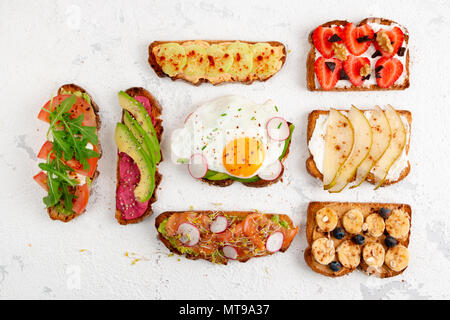 Assortment of healthy breakfast toasts on a white rustic background. Top view, flat lay - Stock Photo