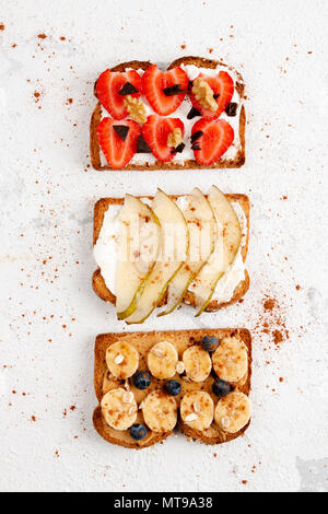 Assortment of healthy fruit toasts with strawberry, banana, pear, blackberries, with cheese cream, peanut butter, honey, cinnamon, chocolate, nuts and - Stock Photo