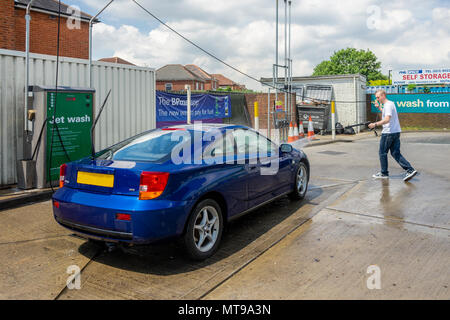 Male (age 30-40 years old) using a hand held jet wash pressure washer to clean a blue Toyata Celica car at a petrol station in the UK, Europe - Stock Photo