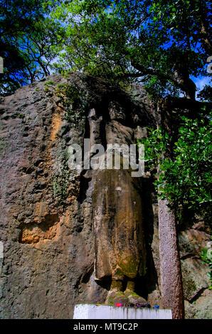 The unfinished Buddha image at Dhowa Raja Maha Vihara rock temple at Bandarawela, Sri Lanka - Stock Photo