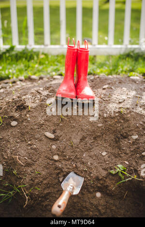 A pair of red, rubber wellies sit in a the dirt in a garden in a backyard. - Stock Photo