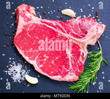 Raw t-bone steak on dark background. - Stock Photo