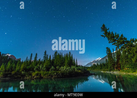 Caption of the North: starry sky in the Bow river valley in Banff national park. Mountains and trees reflected in the blue waters. Campsite, tent. - Stock Photo
