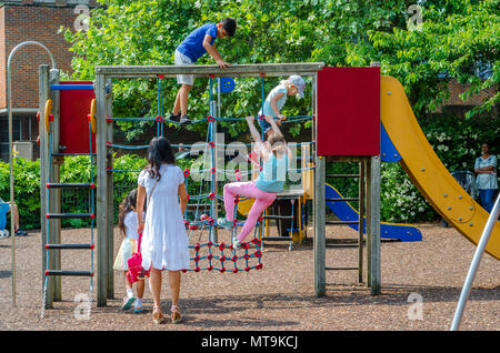 Children climb on a climbing frame and net in the children's playground in Bachelor's Acre in Windsor as a parent watches and supervises. - Stock Photo