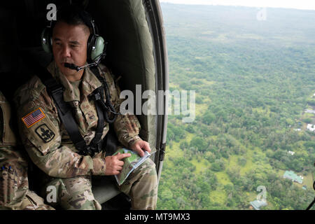 Brig. Gen. Kenneth Hara, Hawaii National Guard deputy adjutant general and Joint Task Force 5-0 commander, observes the ongoing volcanic activity aboard a UH-60 Blackhawk May 7, 2018, while in route to Leilani Estates, Pahoa, Hawaii. Hara is currently serving as a dual status commander, bearing the authority to call upon national guard and active duty resources to aid in the relief efforts. (U.S. Air National Guard photo by Senior Airman John Linzmeier) - Stock Photo
