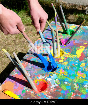 Male hands holding loading brushes with blue paint from ouache paint table covered with colourful smears - Stock Photo