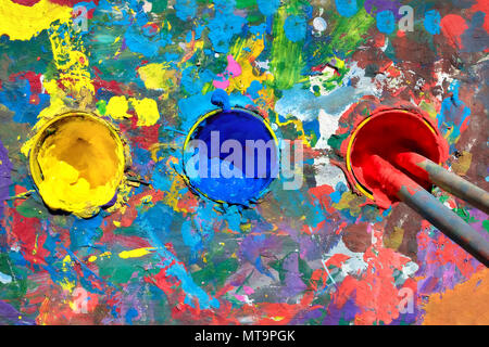 Gouache paint table with paint smears and cups with yellow, blue and red paints. Top view, two brushes in the cup containing in red paint. - Stock Photo