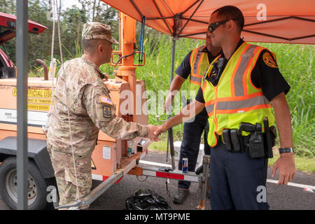 Brig. Gen. Kenneth Hara, Hawaii National Guard deputy adjutant general and Joint Task Force 5-0 commander, visits County of Hawaii police officers at a traffic control point May 18, 2018, at Leilani Estates, Pahoa, Hawaii. Local authorities have been working side-by-side with members of the national guard to provide around-the-clock presence patrols in affected and traffic guidance in response to a volcano outbreak. (U.S. Air National Guard photo by Senior Airman John Linzmeier) - Stock Photo