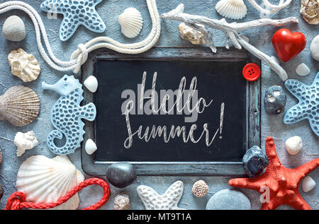 Blackboard with sea shells, stones, rope and star fish on textured light blue background, text 'Hello Summer' in chalk - Stock Photo