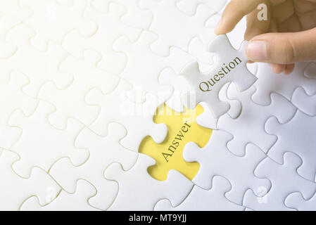 hand holding question and answer word on jigsaw puzzle. q&a, faq and question concept - Stock Photo