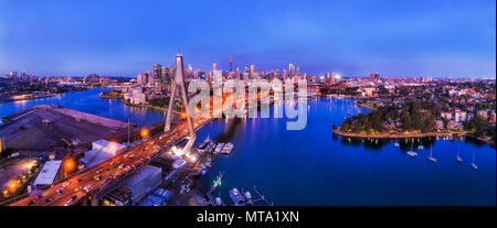 Dark blue time after sunset over Sydney city CBD along ANZAC bridge above Harbour bays and coves in aerial panorama. - Stock Photo