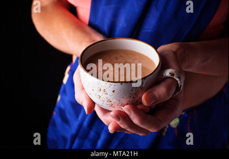 Woman in sari holding a cup of masala chai tea - Stock Photo