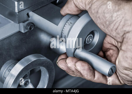 Close-up of control wheels of feed on a machine tool. Detail of a dirty hand on the metal knob with a vernier scale for accurate measuring. - Stock Photo