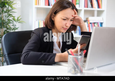 Sad businesswoman working in the office and using smartphone , consulting bad news and needing help - Stock Photo