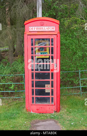 Defibrillator in telephone phone booth box red vintage save life heart attack emergency help in rural countryside Scotland uk - Stock Photo