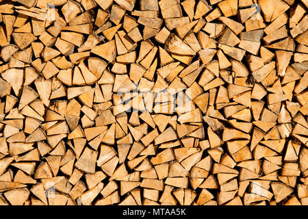 Dry chopped firewood logs ready for winter as background or texture - Stock Photo
