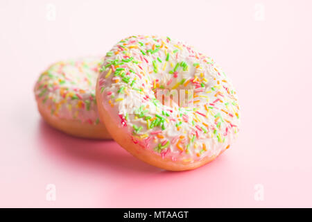Sweet sprinkled donuts on pink background. - Stock Photo