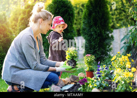 mother and daughter planting flowers together in home garden bed - Stock Photo