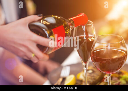 Waiter pouring wine into the glass in restaurant - Stock Photo