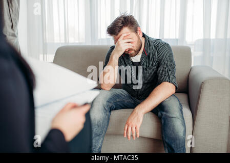 Stressed male patient at psychologist, professional psychology support. Female doctor writes notes in notepad, man sitting on sofa - Stock Photo