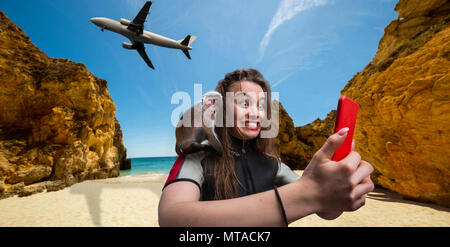 Nice female sportman windsurfer in wetsuit with phone on the beach, monkey sitting on her shoulder, plane flying on background - Stock Photo
