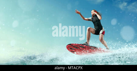 Female sportman windsurfer in wetsuit riding on board and talks by phone - Stock Photo